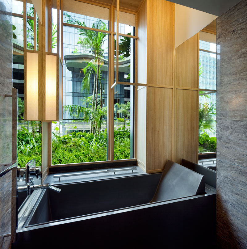 PARKROYAL on Pickering by WOHA - Junior suite bathroom with view looking towards sky terraces