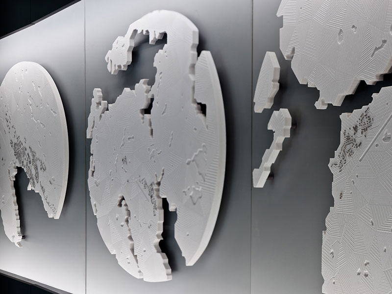 Three of twenty five Corian bas-relief models of Nunavut communities, showing all buildings and roads, the airstrip, rivers and coastline, Arctic Adaptations, 2014