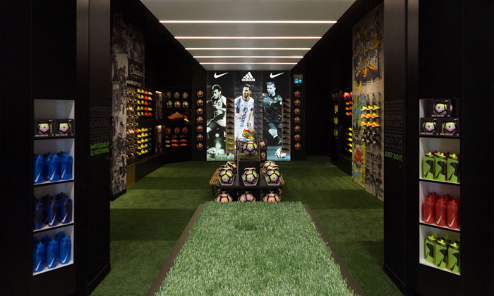 In2Sports Retail Store by Unfold Creative Studio - Threshold into the Boot Room. The linear lighting creates a tunnel effect and puts a focus on the key players in the soccer world.