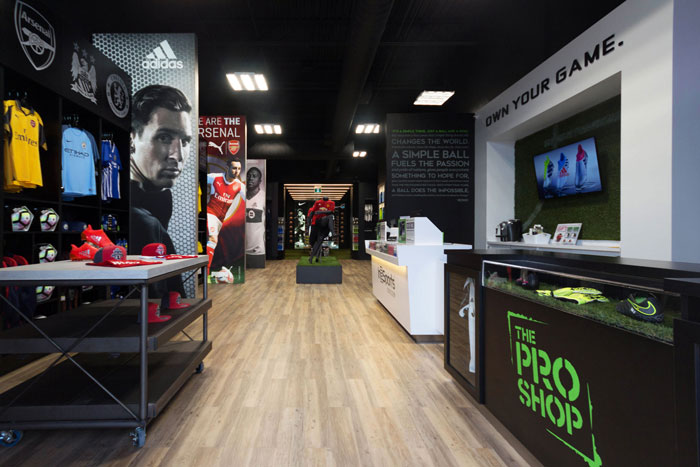 In2Sports Retail Store by Unfold Creative Studio - Entrance of the store. The scale of the custom graphics combined with the lighting effect, create a dynamic atmosphere during the day, and at night
